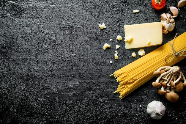 Spaghetti crudi al parmigiano. su sfondo nero rustico