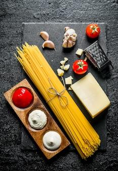 Spaghetti crudi con parmigiano e salse diverse. su sfondo nero rustico