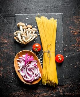 Spaghetti crudi con pomodori, funghi e cipolla da taglio in una ciotola. su rustico