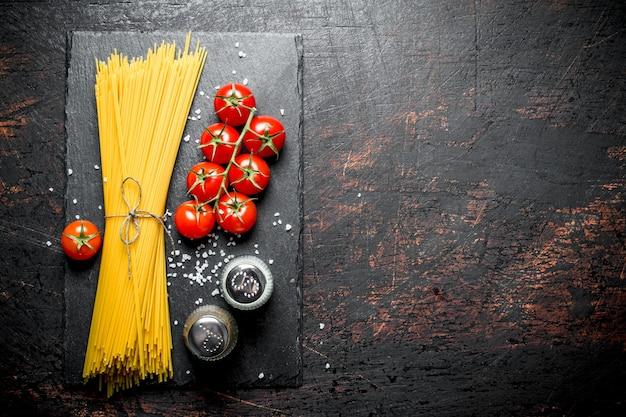 Spaghetti crudi con pomodori e spezie. su fondo rustico
