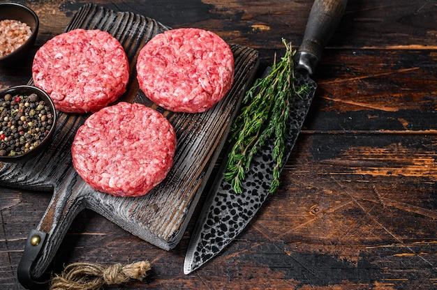 Tortini di hamburger di bistecca cruda con carne macinata e timo su un tagliere di legno