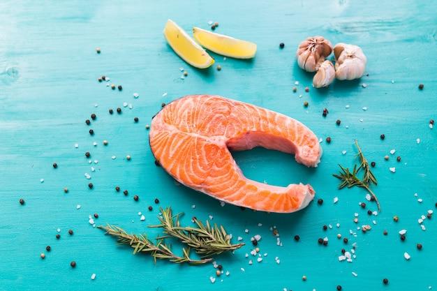 Bistecca cruda di salmone con limone fresco e rosmarino e pepe sulla superficie blu, vista dall'alto. salutare