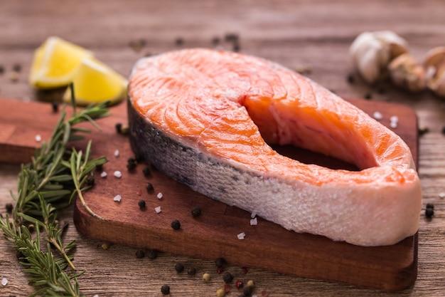 Bistecca cruda di salmone con limone fresco e rosmarino e pepe sulla tavola di legno. concetto di dieta e cibo sano.
