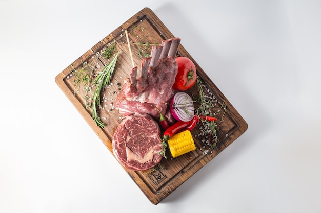 Filetto di manzo crudo con agnello, mais, cipolla, peperoncino, verde e pomodoro su tavola di legno.