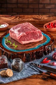 Filetto di manzo crudo (chorizo argentino) su tagliere in legno resinato con spezie. tavolo in legno con sfondo muro di mattoni.