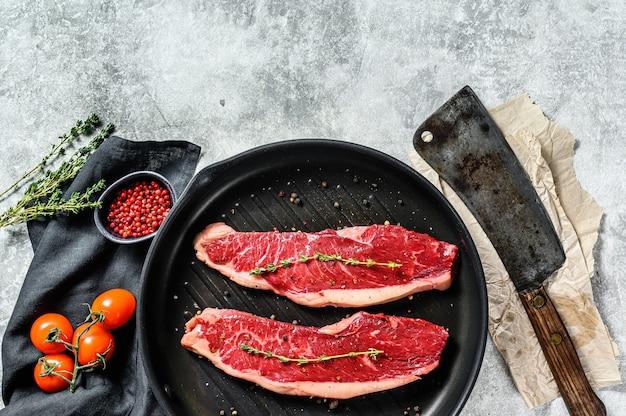 Bistecca di lombo crudo su una bistecchiera, ingredienti per cucinare
