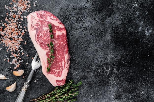 Bistecca di controfiletto crudo su un tavolo da macellaio con sale e timo. sfondo nero. vista dall'alto. copia spazio.