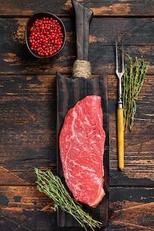 Bistecca di controfiletto crudo su un tagliere, carne di manzo marmorizzata