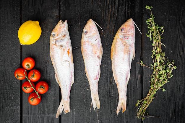 Insieme crudo di pesce intero di frutti di mare di surmulet, con ingredienti ed erbe aromatiche, su fondo di legno nero, vista dall'alto piatta