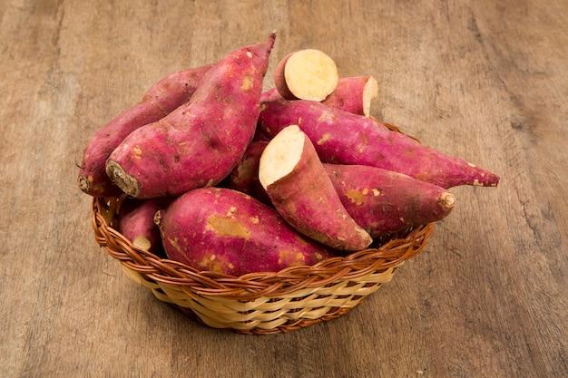 Patate dolci crude sul primo piano di legno dello spazio. verdura fresca.