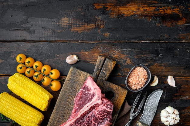 Bistecca alla fiorentina cruda per grill o barbecue con set di ingredienti, sul vecchio tavolo in legno scuro, vista dall'alto laici piatta