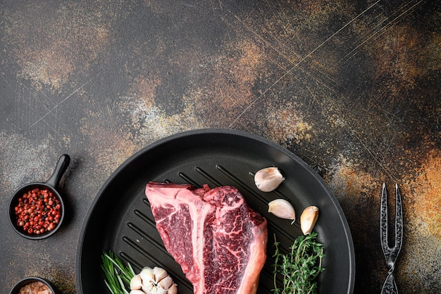 Bistecca con l'osso crudo con set di ingredienti, sulla padella in ghisa, sul vecchio tavolo rustico scuro, vista dall'alto laici piatta