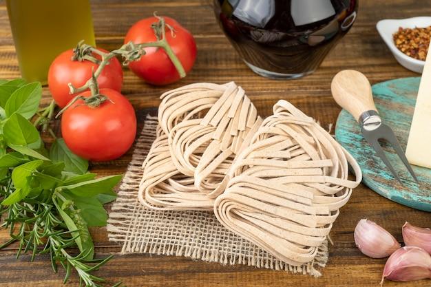 Pasta cruda tagliarini, pomodori, olio d'oliva, vino, pepe ed erbe aromatiche sul tavolo di legno. cucina mediterranea.