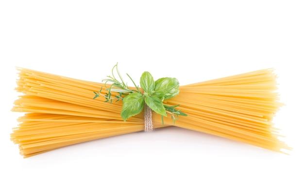 Pasta e basilico crudi delle tagliatelle isolati su bianco isolato.