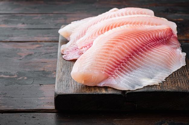 Tagli di carne di filetto di pesce di tilapia cruda, su fondo di legno scuro