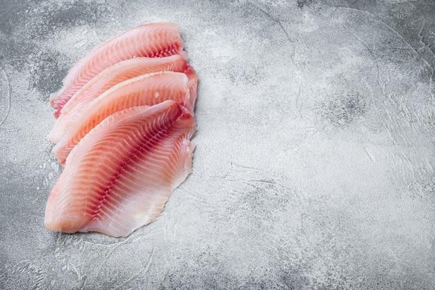 Tagli di carne di filetto di pesce tilapia cruda, su sfondo grigio con spazio di copia per il testo