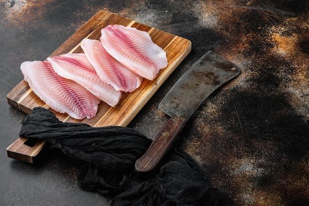 Tagli di carne di filetto di pesce tilapia cruda, sul vecchio fondo rustico con lo spazio della copia per testo