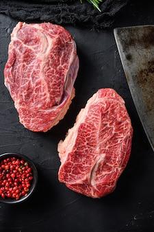 Lama superiore grezza tagliata carne biologica ner macellaio carne coltello intelligente per barbecue o grill vista dall'alto su pietra nera sfondo vicino vista laterale fuoco selettivo