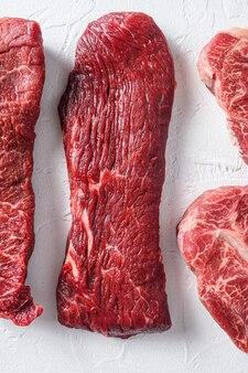 Bistecca cruda tri-punta per barbecue tagliato a base di carne biologica vista dall'alto vicino sul tavolo in cemento bianco verticale.