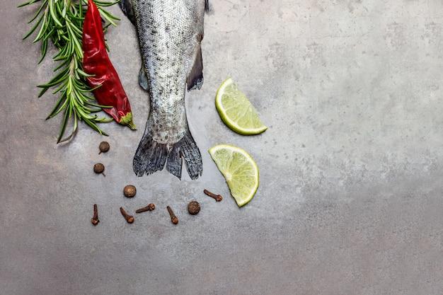 Code di trota crude con rametti di rosmarino, spicchi di limone e pepe. copia spazio. lay piatto