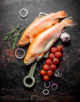 Trota di pesce crudo con anelli di cipolla, pomodori, rosmarino e aglio. su rustico scuro