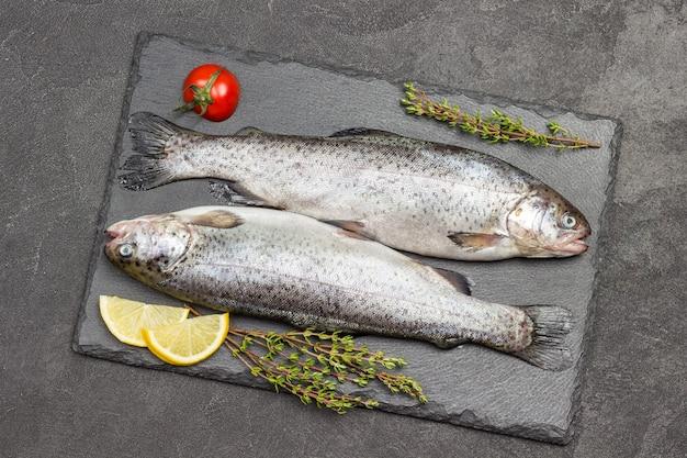 Trota di pesce crudo con rametti di timo e spicchi di limone. lay piatto
