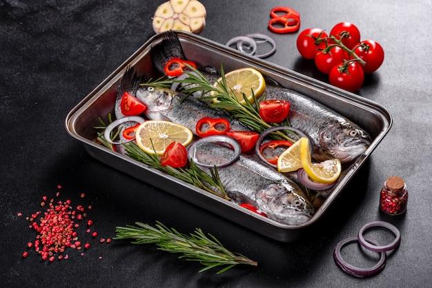 La trota cruda si trova su un tagliere di pietra nera su un tavolo di cemento scuro. nelle vicinanze si trovano: pomodoro, rosmarino, limone, peperone, cipolla, sale