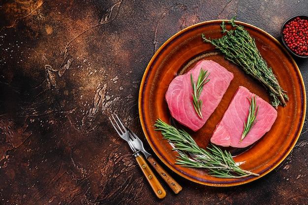 Filetto di tonno crudo con rosmarino e timo su un piatto. sfondo scuro. vista dall'alto. copia spazio.