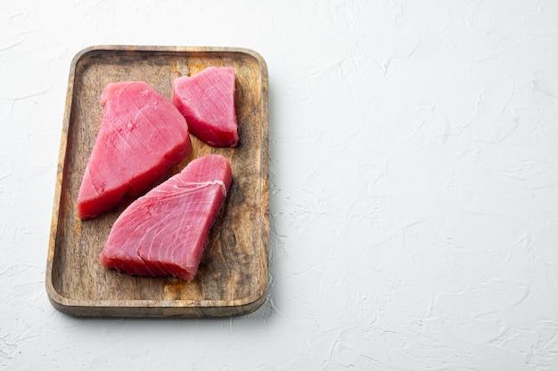 Bistecca di tonno crudo, set di filetti di tonno rosso fresco, su vassoio di legno, su sfondo di pietra bianca, con copyspace e spazio per il testo