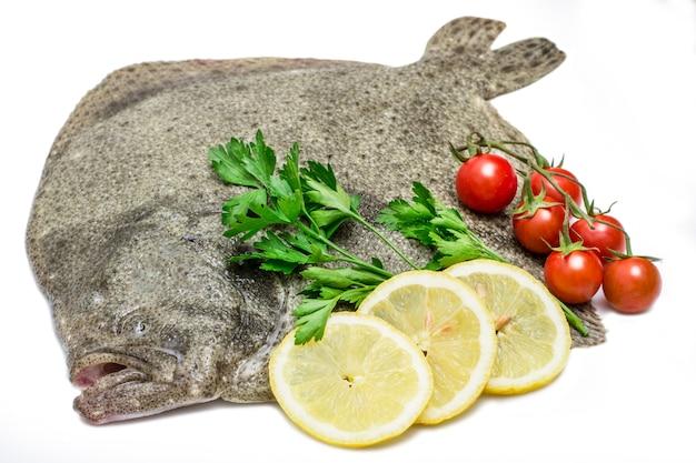 Un pesce rombo crudo con fette di limone, pomodorini e prezzemolo isolato su sfondo bianco