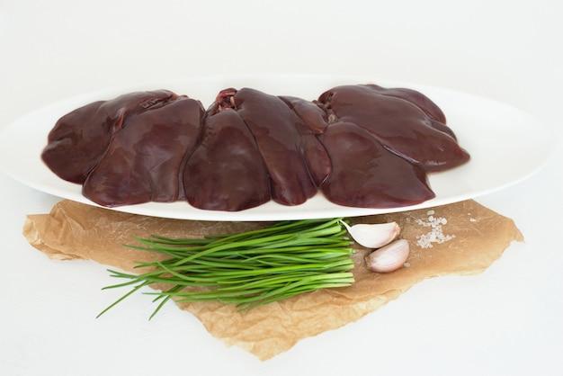 Fegato di tacchino crudo su un piatto bianco interiora di pollo cipolle di erba cipollina