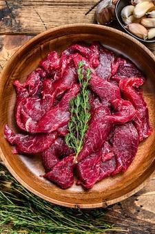 Carne di manzo cruda cruda tagliata a strisce con erbe fresche per manzo alla stroganoff