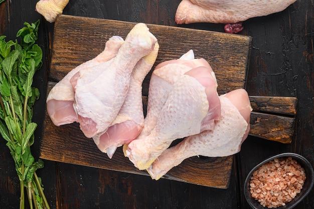 Crudo crudo cosce di pollo, set di bacchette, con condimento ed erbe aromatiche rosmarino e timo, sul vecchio tavolo in legno scuro tavolo, vista dall'alto laici piatta