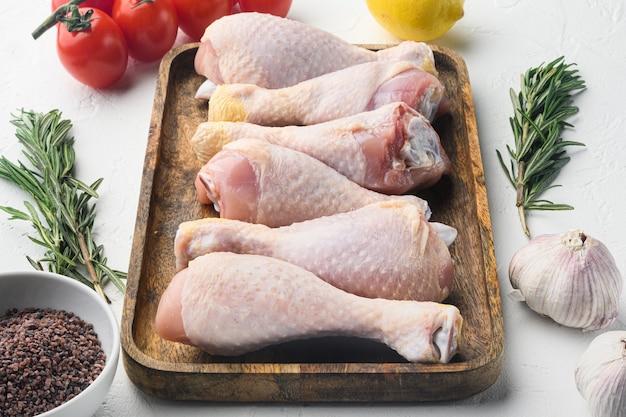 Cosce di pollo crude crude, bacchette con set di ingredienti, con rosmarino, spezie e verdure, sul tavolo bianco