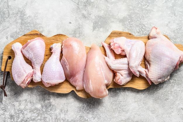 Carne di pollo cruda cruda su un tagliere. sfondo grigio. vista dall'alto.