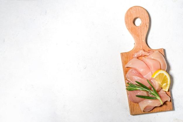Strisce di carne di pollo crudo crudo, filetto di petto crudo fresco a dadini su tavola da cucina vista dall'alto del fondo bianco