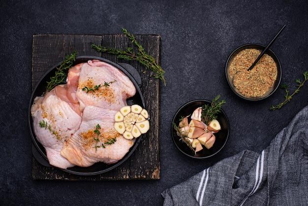 Cosce di pollo crude crude con aglio
