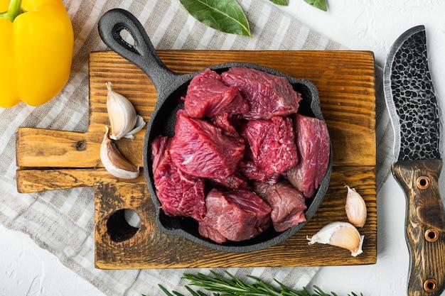 Carne di vitello crudo per spezzatino set con peperone dolce in padella in ghisa