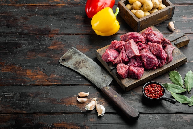 Manzo di vitello crudo per stufato con peperone dolce, sul vecchio tavolo in legno scuro