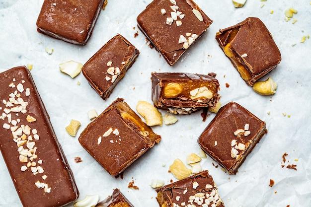 Cioccolato crudo vegano e barrette di caramello, sfondo bianco, vista dall'alto. concetto di dessert sani.