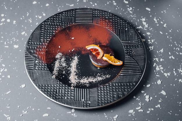 Dessert vegano crudo da frutta secca, composizione di noci e anacardi cremosi, burro di cocco, carruba. sul piatto, isolato su sfondo nero, da vicino