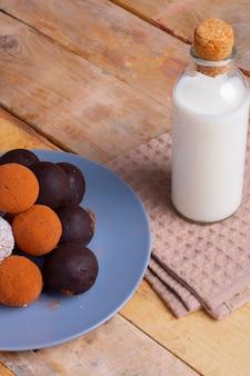 Palle di energia crude, vegane, sane con noci di goji, semi di chia e frutta secca sul piatto blu con latte