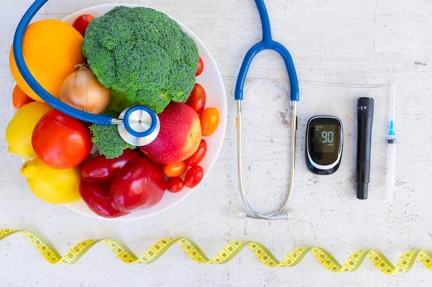Verdure crude e frutta con glucometro e siringa da insulina, concetto di dieta sana del diabete