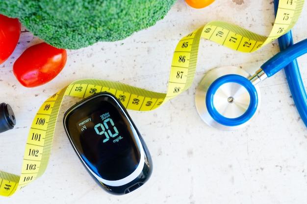 Verdure crude con glucometro e stetoscopio, primi piani, concetto di dieta sana del diabete