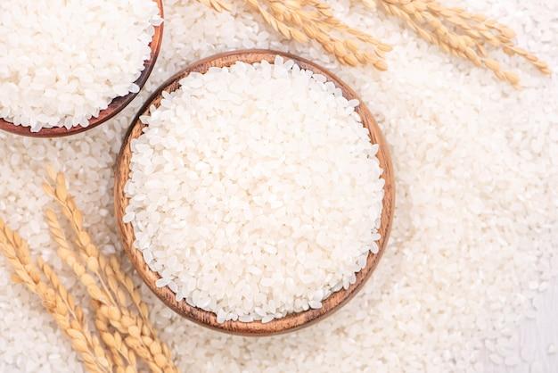 Raccolto di riso commestibile macinato lucidato bianco crudo su fondo bianco in ciotola marrone, concetto di progetto di agricoltura biologica. alimento base dell'asia, primo piano.