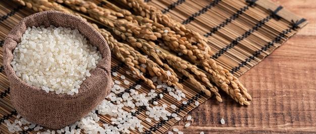 Riso commestibile macinato lucidato bianco crudo sul fondo di legno della tavola in una ciotola, concetto di progetto organico.