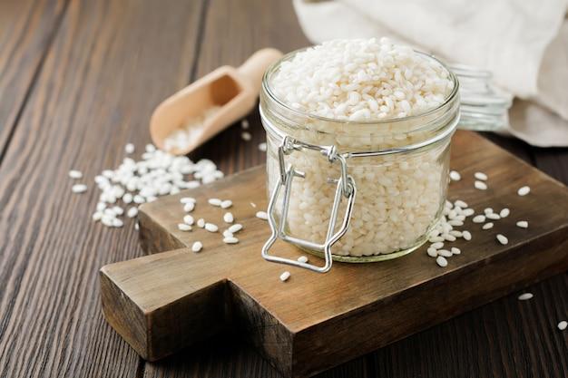 Varietà di riso bianco crudo arborio per risotti italiani in vaso di vetro sulla superficie in legno scuro