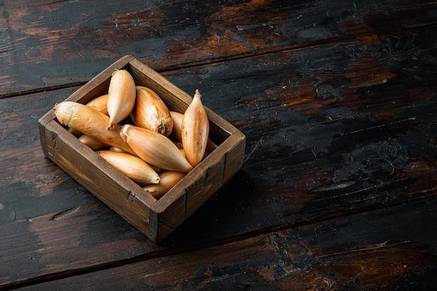 Cipolla intera cruda dello scalogno, sulla vecchia tavola di legno