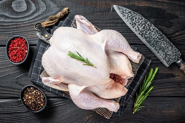 Pollo intero crudo, carne di pollame su una tavola di legno con erbe aromatiche. fondo di legno nero. vista dall'alto.