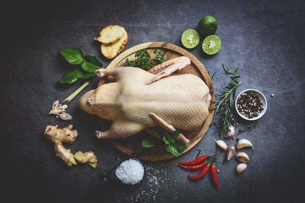 Anatra intera cruda con spezie alle erbe per cucinare al palato scuro, carne di anatra fresca sul vassoio in legno per il cibo